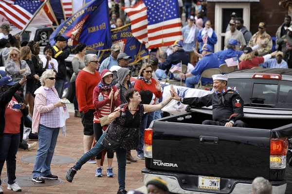 A Navy veteran gets a high-five from a parade spectator during the Veterans Day parade, Saturday, Nov. 11, 2017, in Jacksonville Fla. (Bob Self/The Florida Times-Union via AP)